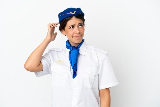 Hôtesse d'avion femme caucasienne isolée sur fond blanc ayant des doutes et avec une expression de visage confuse
