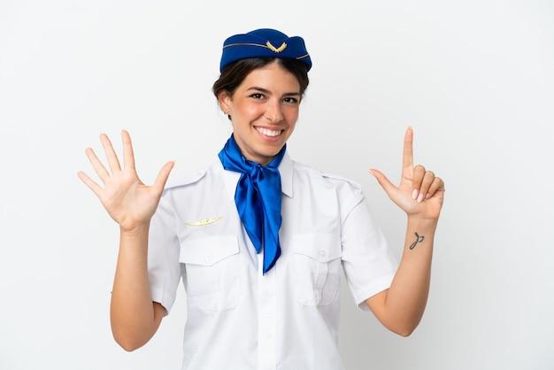 Hôtesse d'avion femme caucasienne isolée sur fond blanc comptant sept avec les doigts