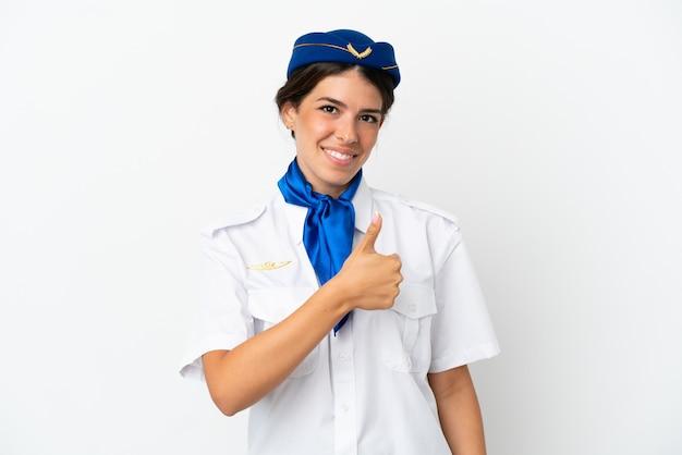 Hôtesse d'avion femme caucasienne isolée sur fond blanc donnant un geste du pouce vers le haut