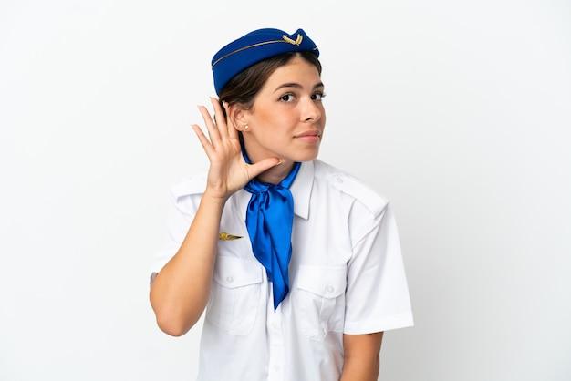 Hôtesse d'avion femme caucasienne isolée sur fond blanc écoutant quelque chose en mettant la main sur l'oreille