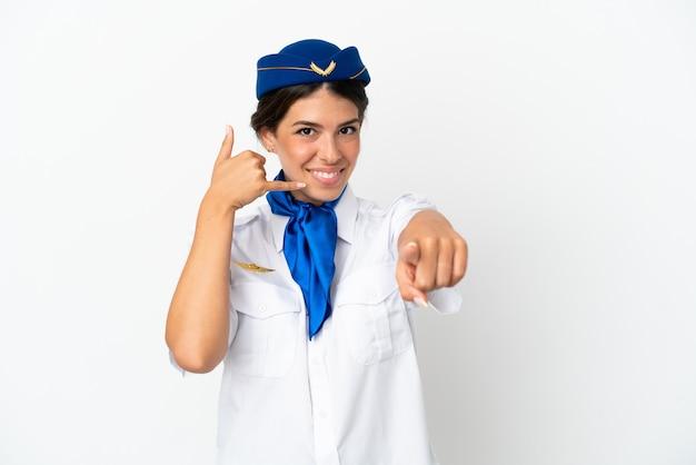 Hôtesse d'avion femme caucasienne isolée sur fond blanc faisant un geste de téléphone et pointant vers l'avant