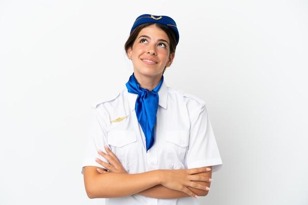 Hôtesse d'avion femme caucasienne isolée sur fond blanc en levant tout en souriant