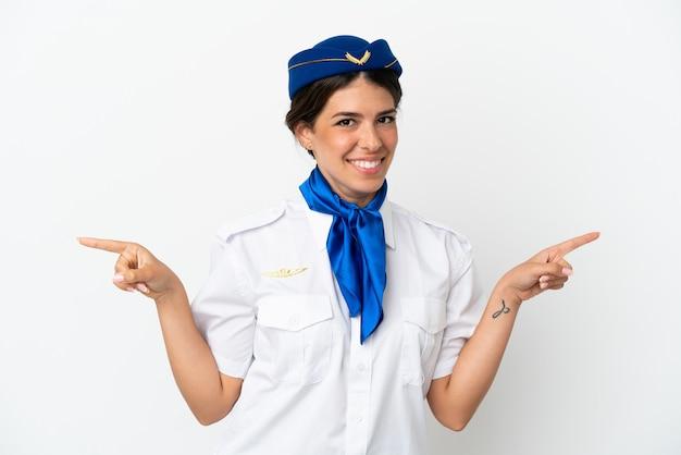 Hôtesse d'avion femme caucasienne isolée sur fond blanc, pointant le doigt vers les latéraux et heureux