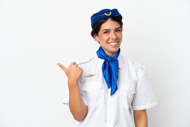 Hôtesse d'avion femme caucasienne isolée sur fond blanc pointant vers le côté pour présenter un produit