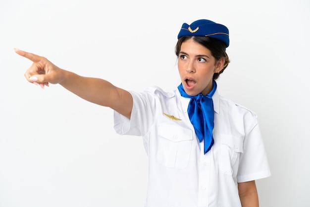 Hôtesse d'avion femme caucasienne isolée sur fond blanc pointant vers l'extérieur