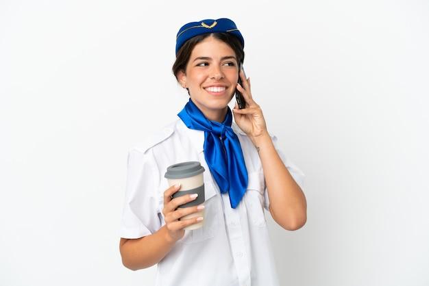 Hôtesse d'avion femme caucasienne isolée sur fond blanc tenant du café à emporter et un mobile