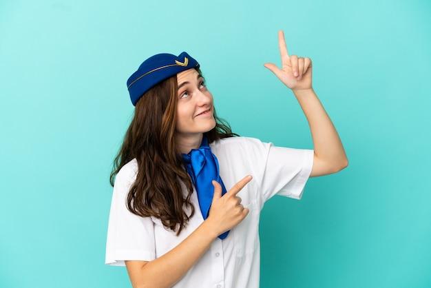 Hôtesse d'avion femme isolée sur fond bleu pointant avec l'index une excellente idée