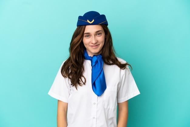 Hôtesse d'avion femme isolée sur fond bleu en riant