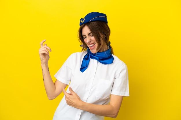 Hôtesse d'avion femme isolée sur fond jaune faisant un geste de guitare