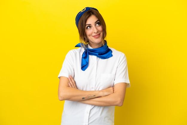 Hôtesse d'avion femme isolée sur fond jaune en levant tout en souriant