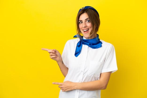 Hôtesse d'avion femme isolée sur fond jaune surpris et pointant du côté