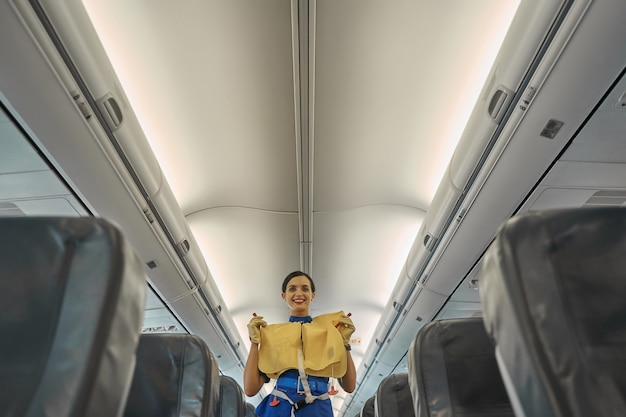 Hôtesse de compagnie aérienne joyeuse tenant un gilet de sauvetage et souriant tout en donnant des instructions de sécurité avant le vol