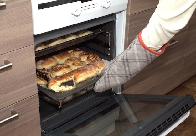 L'hôtesse tire des gâteaux, des petits pains et des petits pains avec des graines de pavot de la cuisinière de cuisine tenant une casserole avec gant