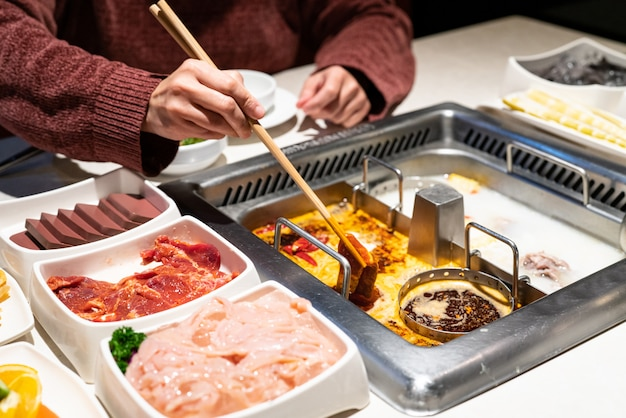 Hotpot chinois shabu soupe épicée et aigre avec de la viande et des fruits de mer, style chinois suki - selective focus