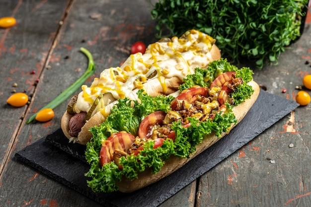 Hots dogs grillés gastronomiques avec garnitures assorties. bannière, menu, lieu de recette pour le texte, vue de dessus.
