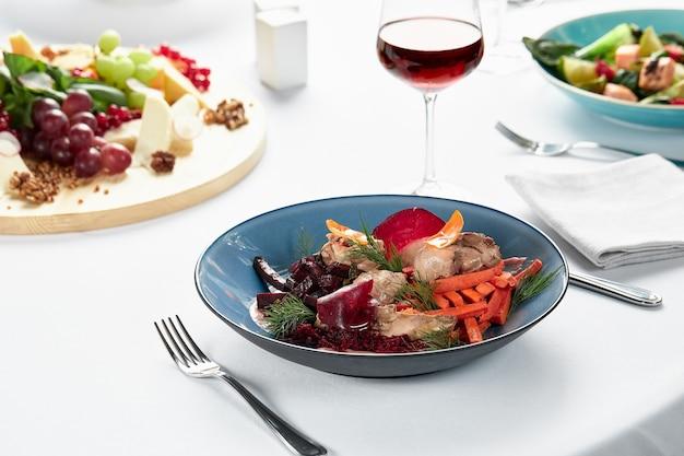 Houmous aux légumes, houmous de betteraves avec bâtonnets de légumes frits et feuilles de svela, une table de fête avec des collations et du vin.