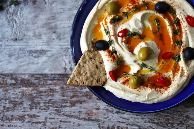 Houmous aux olives, paprika et huile d'olive sur une plaque. assiette bleue servant du houmous.