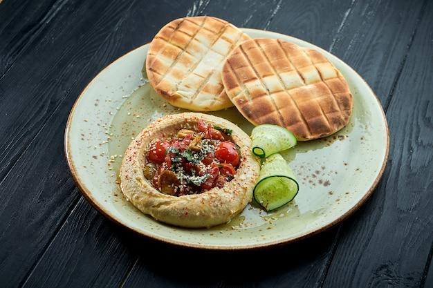 Houmous aux pois chiches avec tomate au four et huile d'olive servi avec pita au four dans une assiette sur un fond de bois sombre.