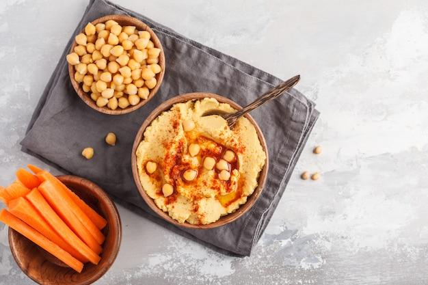 Houmous, bâtonnets de carottes fraîches et pois chiches cuits dans des bols en bois. concept de cuisine végétalienne, fond clair, espace copie, vue de dessus