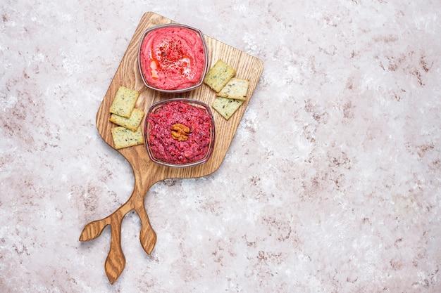 Houmous de betterave sur une planche à découper avec des biscuits salés sur une surface claire