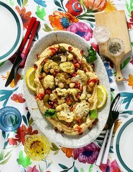 Houmous avec chou-fleur cuit au four et graines de grenade sur une table avec une nappe aux couleurs vives