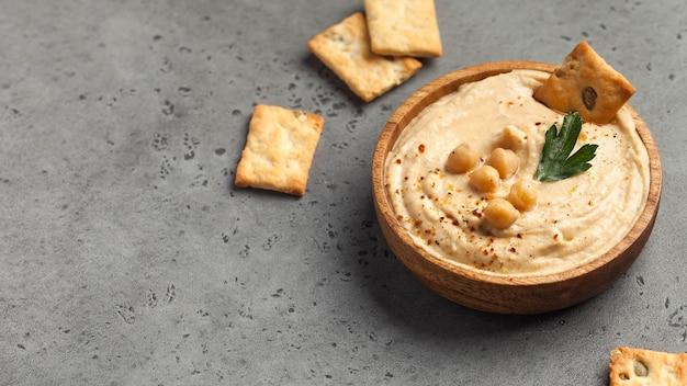 Houmous dans une assiette en bois avec du persil et des croûtons