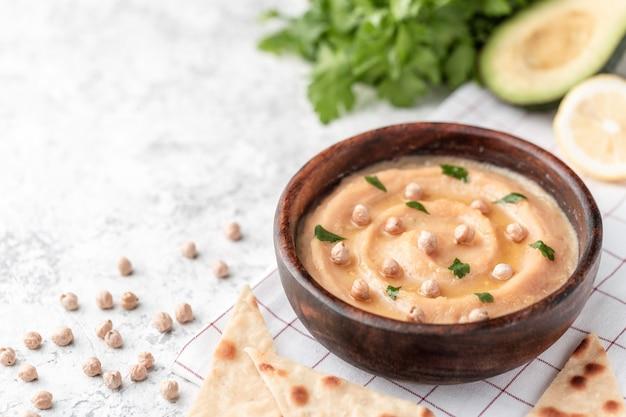Houmous dans une assiette en bois marron. sur la table blanche sont des légumes, des verts, des morceaux de pita triangulaires.