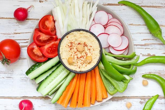 Houmous dans un bol, bâtonnets de légumes, pois chiches, olives.