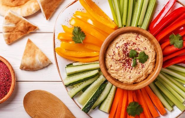 Houmous maison sain avec un assortiment de légumes frais et de pain pita.