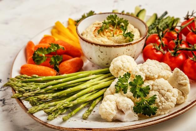 Houmous maison sain avec un assortiment de légumes frais.