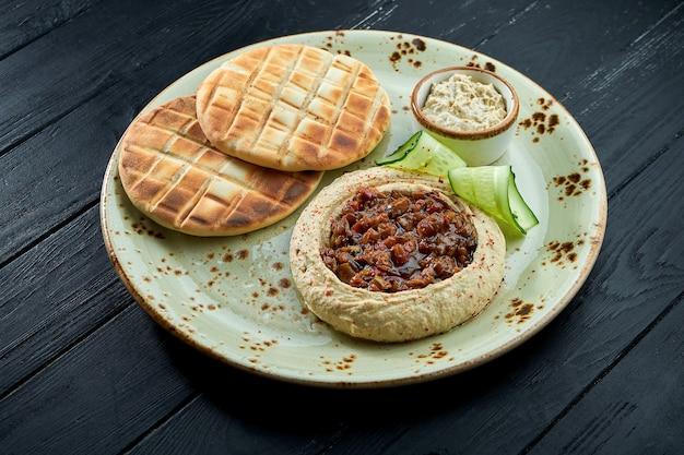 Houmous de pois chiches aux légumes cuits au four et huile d'olive servi avec pita cuit au four dans une assiette sur un fond de bois sombre.