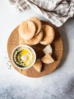 Houmous de pois chiches maison traditionnel, arrosé d'huile d'olive et de persil frais et de tranches de pita fraîches sur une planche à découper en bois. espace copie