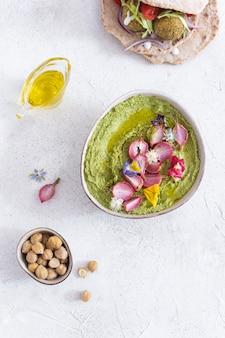 Houmous vert avec radis cuit au four et fleurs comestibles