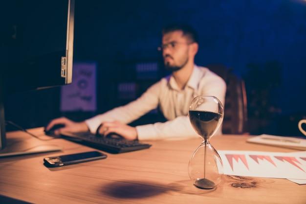 Hourglass debout sur la table à côté de l'entrepreneur en tapant pc