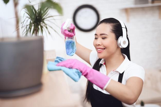 Housekeper essuie la poussière des meubles dans la chambre