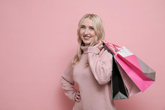 Hppy belle femme blonde en pull rose tenant des sacs à provisions. concept de magasinage heureux