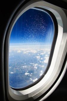 Hublot recouvert de cristaux de glace. vue sur les alpes depuis l'avion.