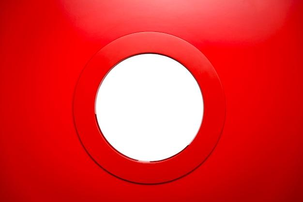 Hublot rond blanc dans la porte rouge.
