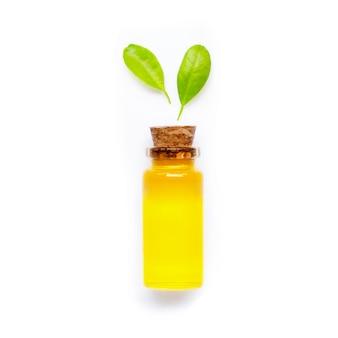 Huile d'agrumes naturelle avec des feuilles vertes sur fond blanc. haute vitamine c.