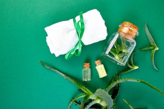 Huile d'aloe vera en bouteille de verre et serviette de spa