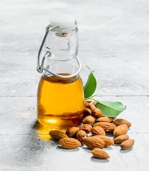 L'huile d'amande dans une bouteille en verre sur table rustique.