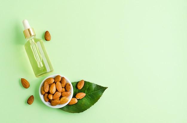 Huile d'amande plate et noix entière pour soins de la peau, massage, cuisson sur fond vert.