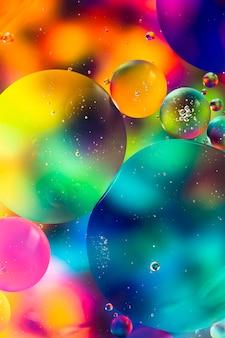 L'huile d'arc-en-ciel tombe sur un fond abstrait de la surface de l'eau