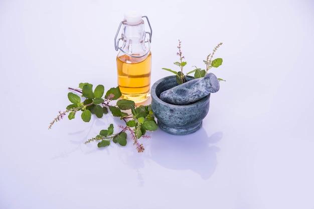 Huile ayurvédique de tulsi, extrait de reine des herbes dans une bouteille en verre avec des branches de basilic sacré vert frais et un mortier avec un pilon. isolé sur fond coloré. mise au point sélective