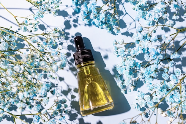 Huile de beauté aux ingrédients naturels sur fond bleu avec des fleurs. concept de traitement de soins de la peau. paquet sans marque pour la conception