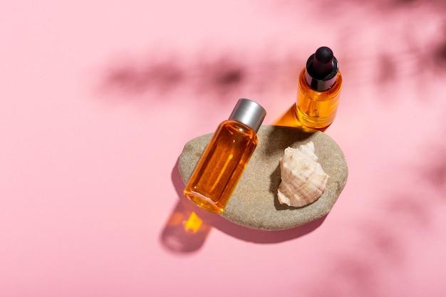 Huile de bronzage. produits cosmétiques à côté de coquillages dans les rayons du soleil sur fond rose. cosmétiques protecteurs solaires.