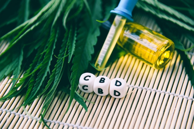 Huile de cannabis en bouteille produits fond en bois huile de cbd feuille de cannabis feuilles de marijuana pour les soins médicaux de chanvre
