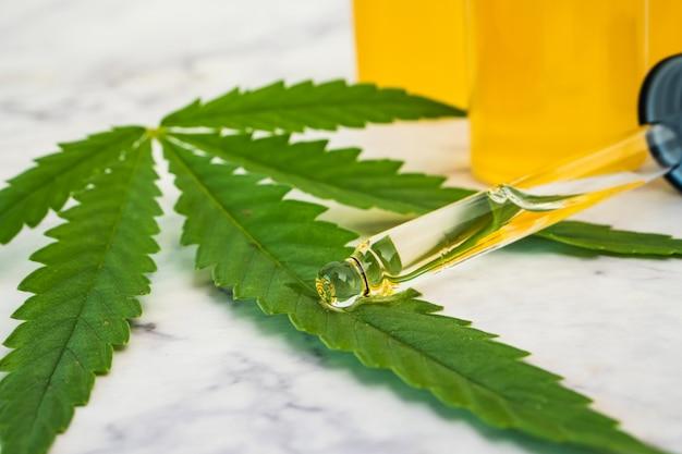 Huile de cannabis dans les flacons avec tube compte-gouttes et feuille verte sur table en marbre. concept de médecine alternative.