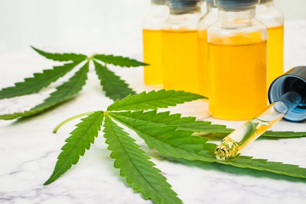 Huile de cannabis dans les flacons avec tube compte-gouttes et feuilles vertes sur table en marbre. concept de médecine alternative.