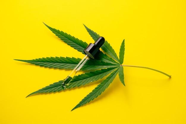 Huile de cannabis dans le tube compte-gouttes avec feuille verte sur fond jaune. concept de médecine alternative.